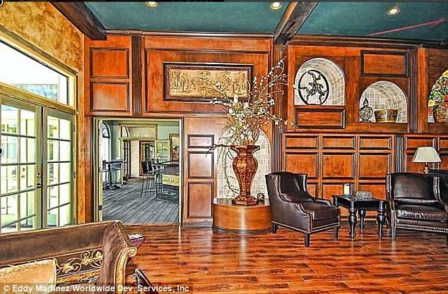 Caloroso e acolhedor: uma sala de estar ostenta piso e paredes de madeira e bancos de couro confortáveis