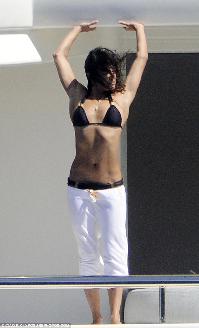 Living on the edge: Michelle unveils her toned abs as she enjoys a stretch on the deck