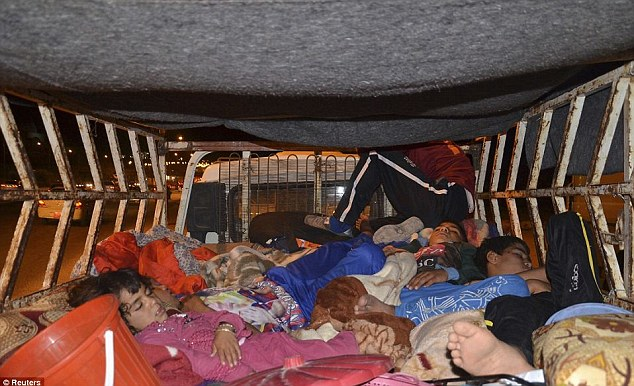 Long journey: Children sleep in the back of a truck which took them from the fighting to the safety of Kurdistan