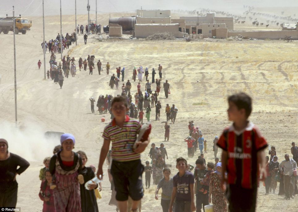 Members of the Yazidi community walk towards the Syrian border, on the outskirts of the Sinjar mountains, near the Syrian border town of Elierbeh of Al-Hasakah Governorate on Sunday
