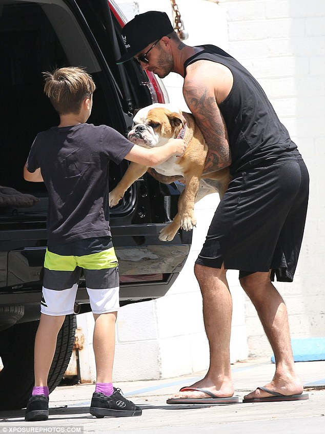 David Beckham Carries Daughter Harper As He Heads Out With
