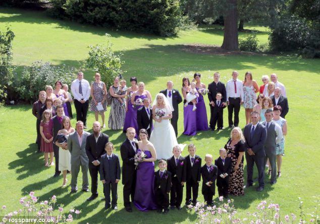 Convidados e os noivos posar para uma foto no casamento da dupla no Makeneny Hall Hotel em Belper