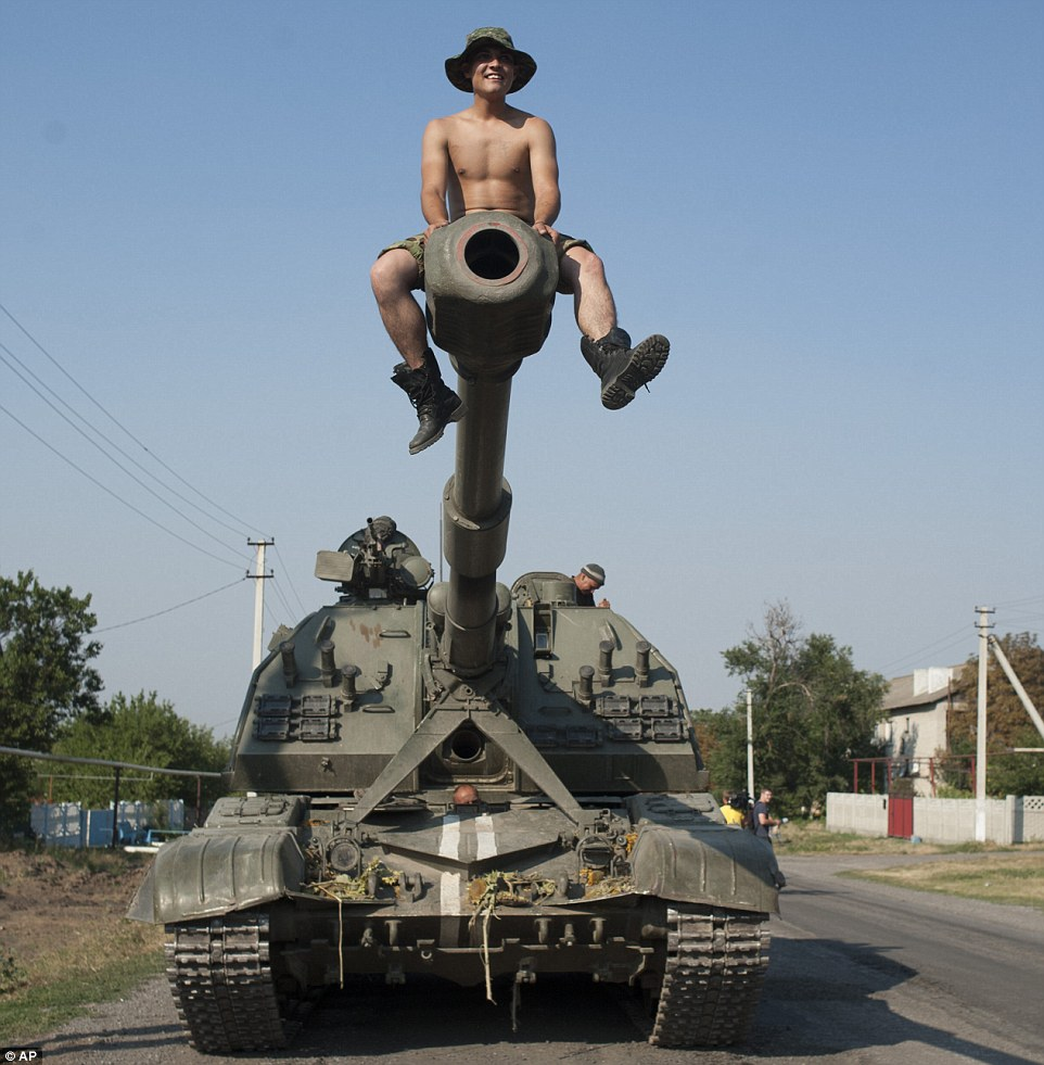 Heavy arms: A Ukrainian soldier sits atop a self-propelled artillery gun headed towards Donetsk, which has been shelled for several days