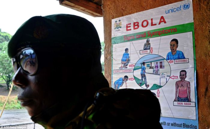 A soldier from Sierra Leone stands near an Ebola information poster in Kenema district, which is being described as the 'epicentre' of the outbreak