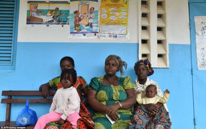 A group of women and children wait outside a health centre in Kandopleu, Ivory Coast near the border with affected Ebola countries Guinea and Liberia