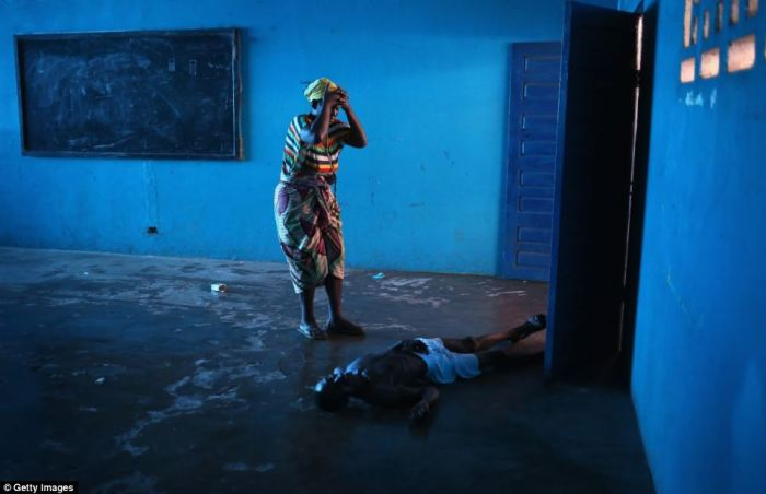 A woman stands over her husband with her head in her hands, after he staggered and fell, knocking him unconscious in an Ebola ward in Liberia