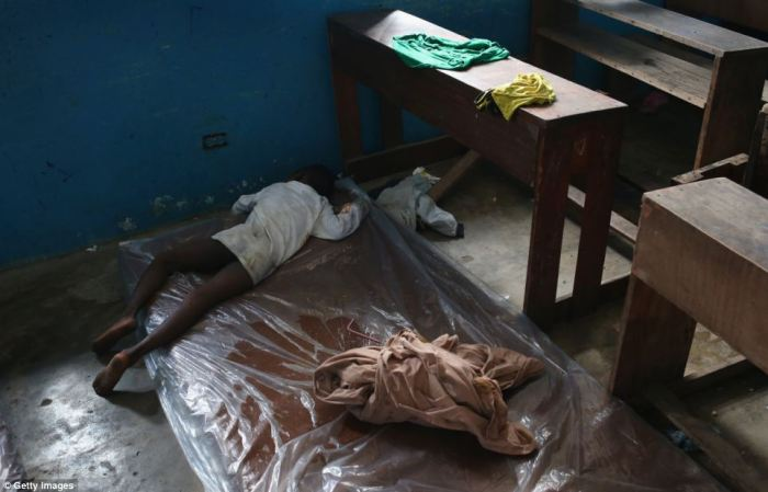 A sick child lies on a mattress in a former classroom in a primary school, which has been transformed into an Ebola ward