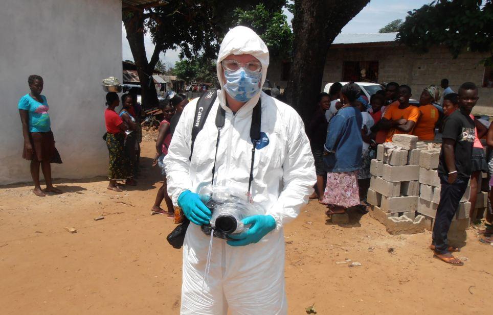 Getty Imágenes fotógrafo personal de John Moore usa ropa protectora, sabe como el equipo de protección personal (PPE), antes de unirse a un equipo de enterramiento de Liberia establecido para retirar el cuerpo de una víctima del Ébola desde su casa
