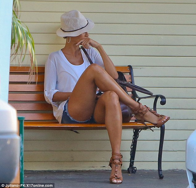 Rest: Nicole displays her killer heels as she waits outside on a bench