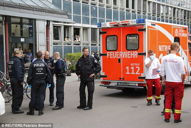 Quarantined: Police officers and ambulance medical staff stand outside the jobcentre in the Berlin district of Pankow after a woman showed symptoms of the infectious Ebola virus disease then collapsed there