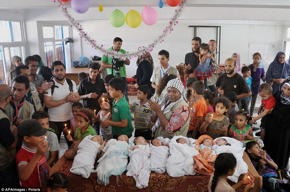 Joyous occasion: The babies slept soundly as they were greeted by well-wishers at the ceremony, no doubt pleased to have a respite from fighting which has robbed many of them of their homes