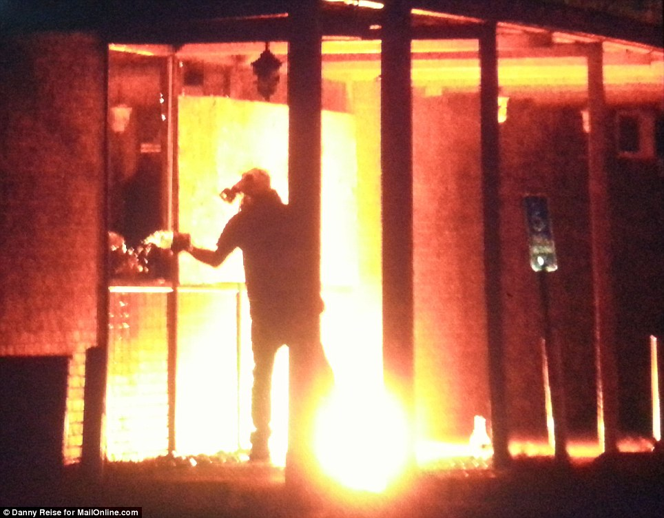Protester pours fuel into Red BBQ restaurant, after a previous Molotov cocktail he threw burns outside the building. The fire outside was put out by fellow protesters, Ferguson, Missouri on Monday night