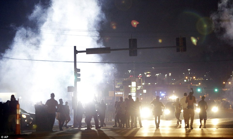 Protesters walk through a cloud of tear gas during Monday's disturbances in Ferguson