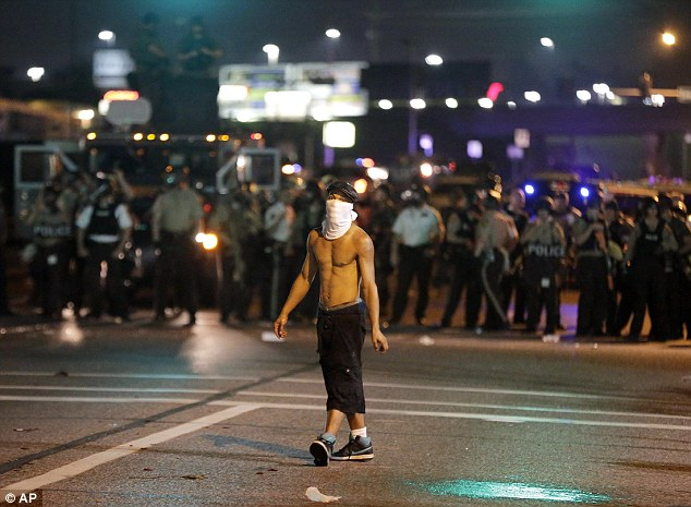 A lone man walks in front of police lines in Ferguson as 31 people are reported to have been arrested
