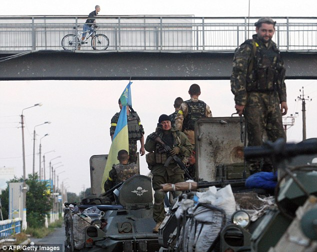 Ready for battle: If the claims that tanks, artillery and 1,200 men had come into Lugansk from Russia are true then these Ukrainian servicemen will soon have a big fight on their hands. Russia denies arming separatists