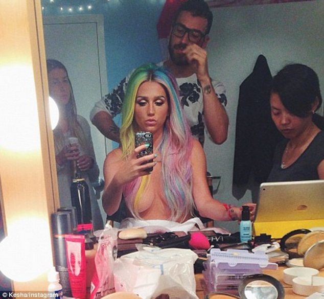 Not shy: A topless Kesha posted this picture of herself surrounded by her glam squad before the big night
