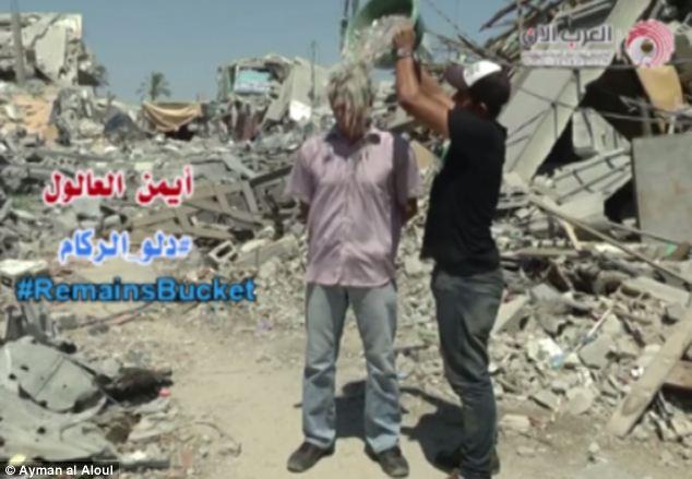 Débrouillardise: Au lieu de l'eau, il demande aux participants à la pointe des seaux remplis de gravats sur leurs têtes.  La vidéo, filmée au milieu d'une rue de Gaza détruite par les bombes, a été téléchargé sur Facebook vendredi