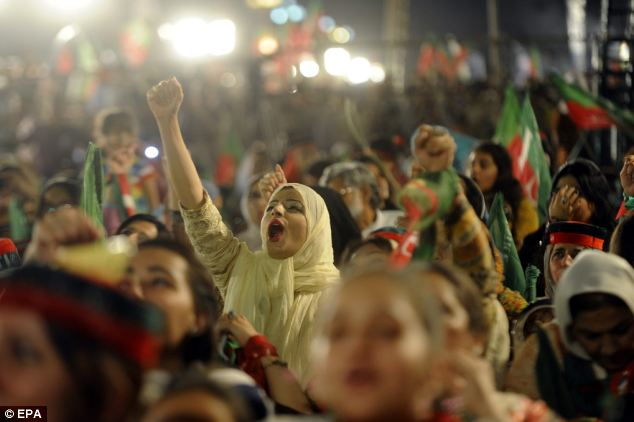 Supporters of Imran Khan, the former International cricketer turned politician, listen to his speech during an anti-government protest in front of Mr Sharif's home in Islamabad