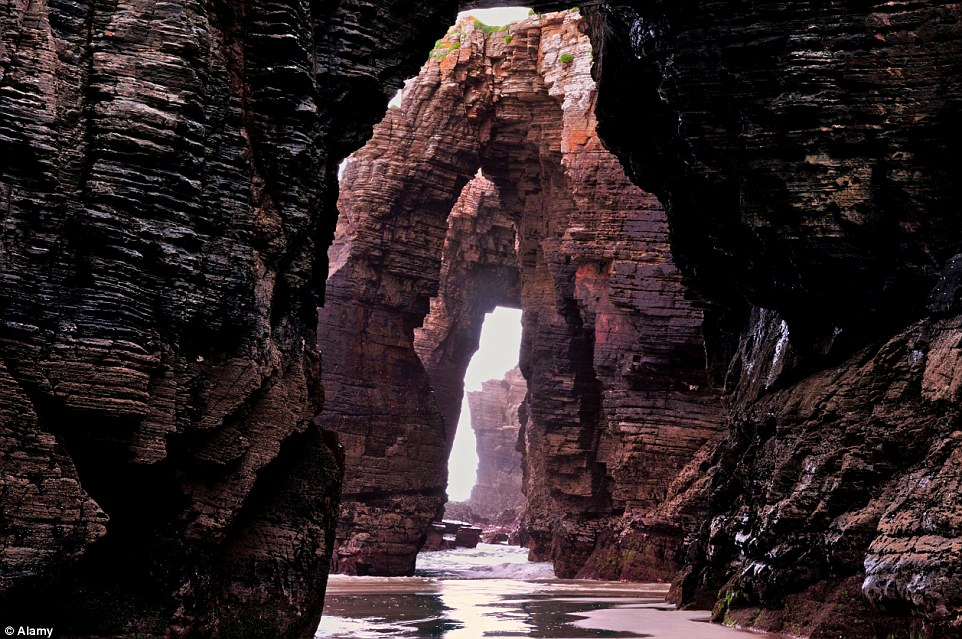 Magnificent: Cathedral-like arches are pictured at low tide at Praia As Catedrais ('beach of the cathedrals') near Ribadeo, Spain