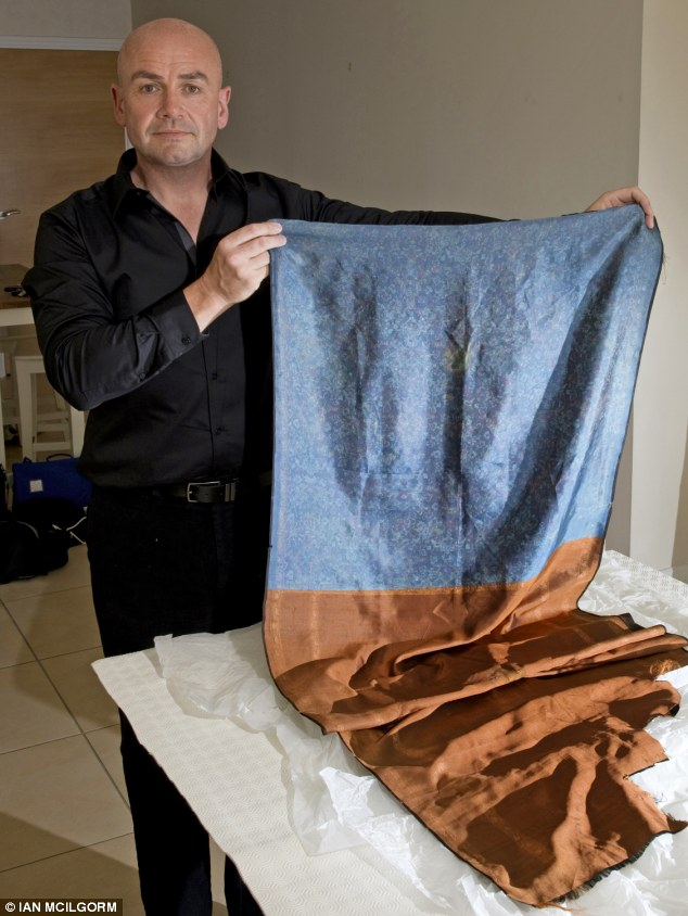 Found at the scene: Russell Edwards holds the shawl he bought in 2007, allegedly handed down from a policeman who took it from the scene, which had the incriminating DNA on it