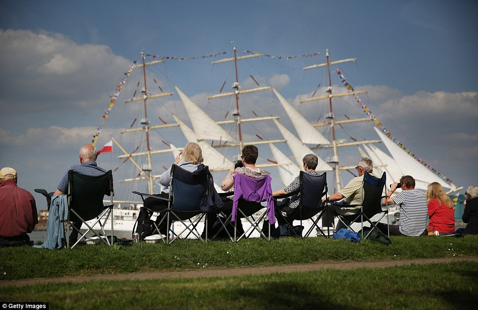 A group of spectators set up chairs on the river's edge to catch  a glimpse of the parade. The white sails of the Dar Mlodziezy are in the background
