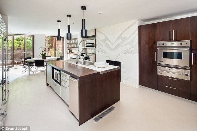 Cook up a storm: The first Garden Floor has a kitchen a kitchen stocked with stainless steel appliances that contrast to the warm walnut wood eat-in area and access to the tiered garden