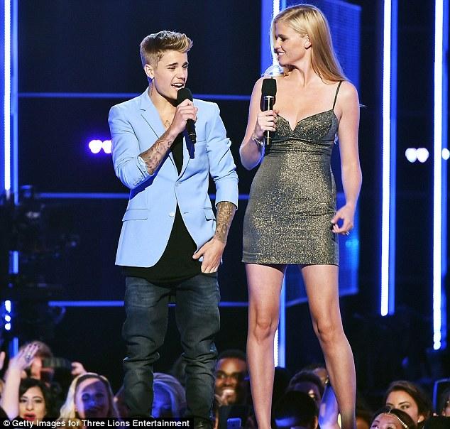 Fully dressed: Justin Bieber in a powder blue coat, black tank-top and dark jeans, lara Stone | ozara gossip