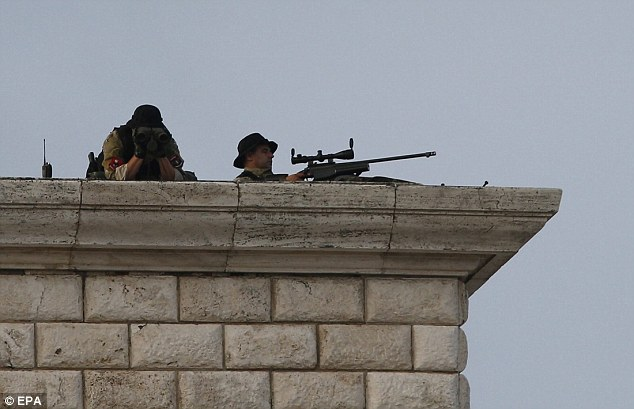 Snipers watch on from a building roof as crowds gather below for the Holy Mass which will take place today