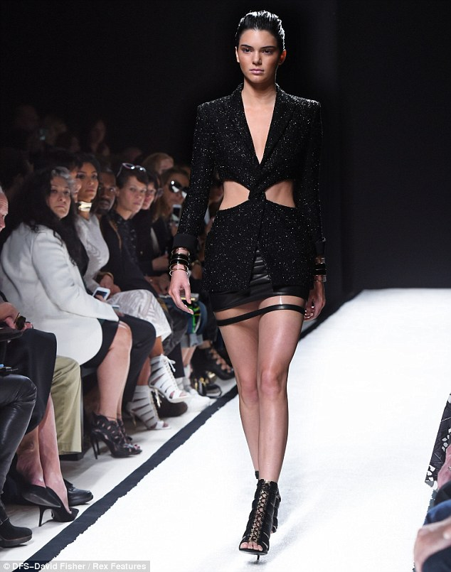 Eyeing: Kim was seen casting an eye over her sister's ensemble as she made her way down the runway