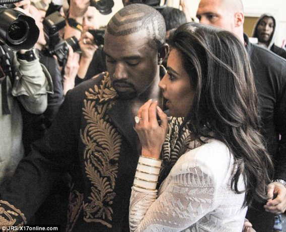 Protective: Kanye West put a protective arm around his shaken wife after the terrifying incident