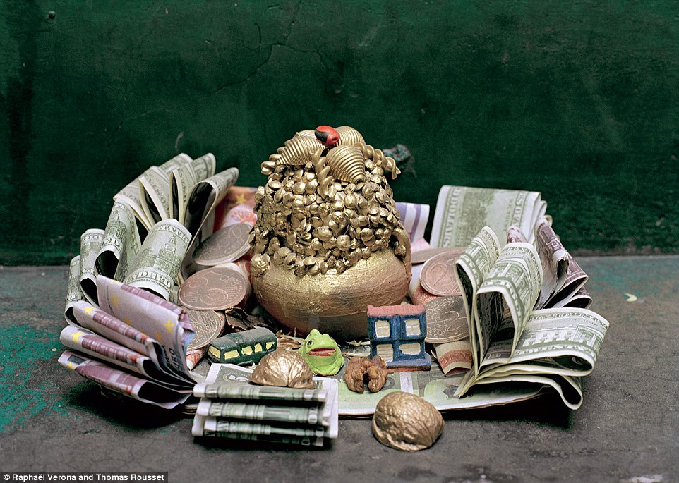 Goods: These offerings to the Catholic and Aymara spirits include money, nut shells, an ornate gold statue and small models of a house, a bus and a green frog