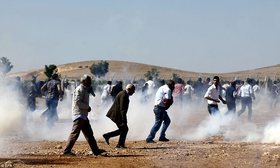 Desperation: Elderly Kurds walk though clouds of tear gas near the Syrian border today after staging protests against ISIS attacks on their hometown