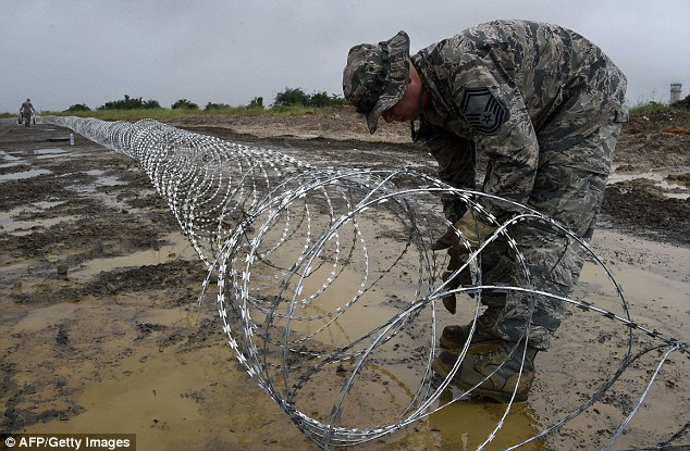 Poor infrastructure, difficulties with equipment and torrential rains slowed the U.S. military's initial response, but by Monday afternoon U.S. soldiers had started to erect barbed wire around what will be one of almost 20 treatment centers