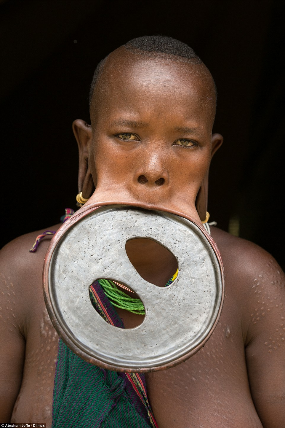Ataye Eligidagne, 20, dons the largest lip disc in the world. The hardened clay disc is 59.5 cm in circumference and 19.5 cm in diameter