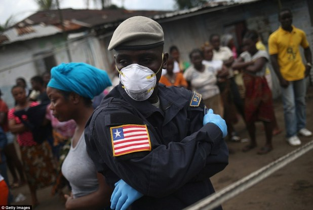 Keeping watch: A Liberian policeman is pictured watching as an Ebola burial team prepares to take away the body of Ms Nagbe