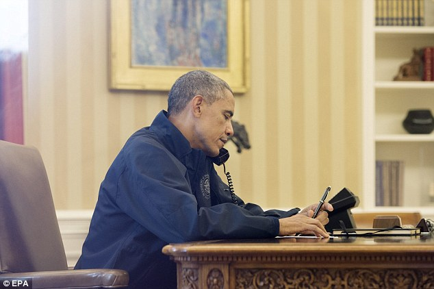 Briefly briefed: President Barack Obama speaks on the phone with Health and Human Services Secretary Sylvia Burwell, to get an update on the response to the Ebola diagnosis in Dallas, in the Oval Office of the White House in Washington DC Sunday before taking off for a round of golf