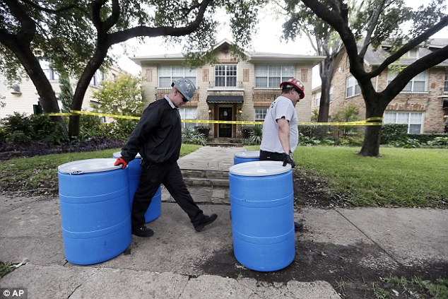 Hazard: Protect Environmental workers move disposal barrels to a staging area outside the Dallas apartment of Miss Pham