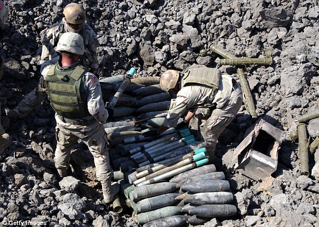 Cache: Isis controls a compound in Iraq containing 2,500 chemical weapons rockets, according to the Iraqi government. Pictured are Navy Explosive Ordnance Disposal technicians preparing unexploded ordnance for demolition at a safe disposal area near Baghdad in 2003
