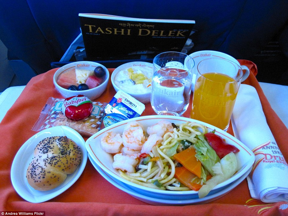 Drukair, the national carrier of Bhutan serves a sizeable meal for its business class passengers of stir-fried noodles with vegetables and prawns, and a poppy seed roll. Orange juice or water to drink as well as a serving of fruit salad and creamy yoghurt.