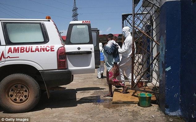Un trabajador de salud acompañantes una madre y su bebé de un centro de detención en Monrovia en una ambulancia para el transporte a un centro de tratamiento