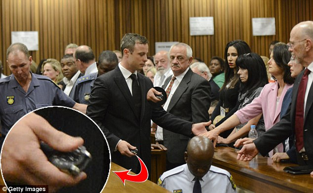 Saving his possessions: The runner takes his watch off before being led down to the cells below the courtroom