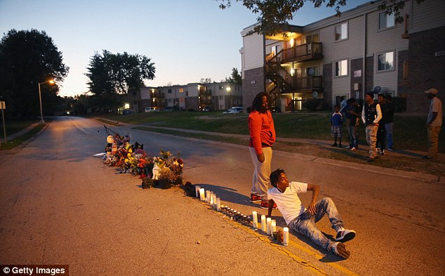 Vigils: Demonstrators - pictured on October 20 - have continually held vigils for Brown since the shooting in August. They are pictured above on Canfield Street, where he died
