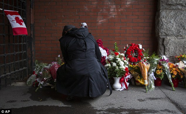 Shock: A mourner lays flowers at a memorial in Hamilton, Ontario