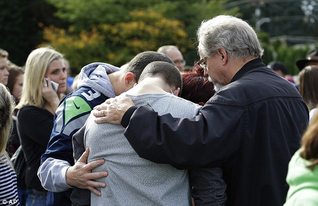 Devastated: People embrace in a circle at a church after the deadly school shooting