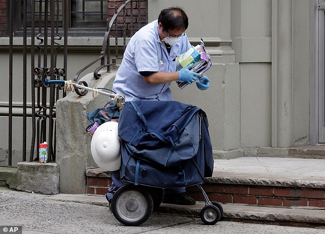 Postal worker Keven Ngo, wearing a protective mask and gloves, prepares to deliver to the apartment building of Ebola patient Dr. Craig Spencer in Harlem