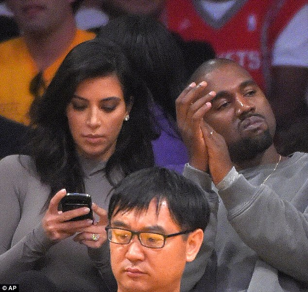 Engrossed: The star was glued to her phone throughout the night, while her husband Kanye enjoyed the game
