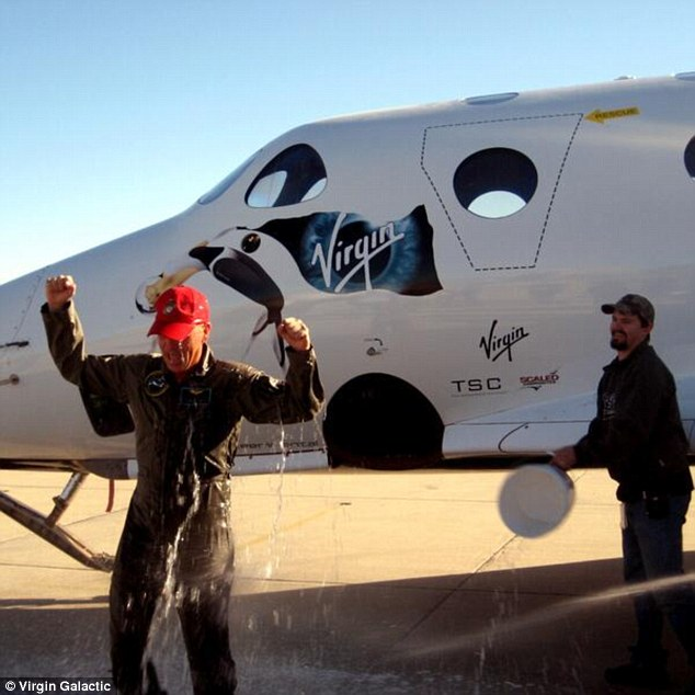 CJ Sturckow gets splashed with water after guiding Virgin Galactic's private SpaceShipTwo through an unpowered 'glide flight'