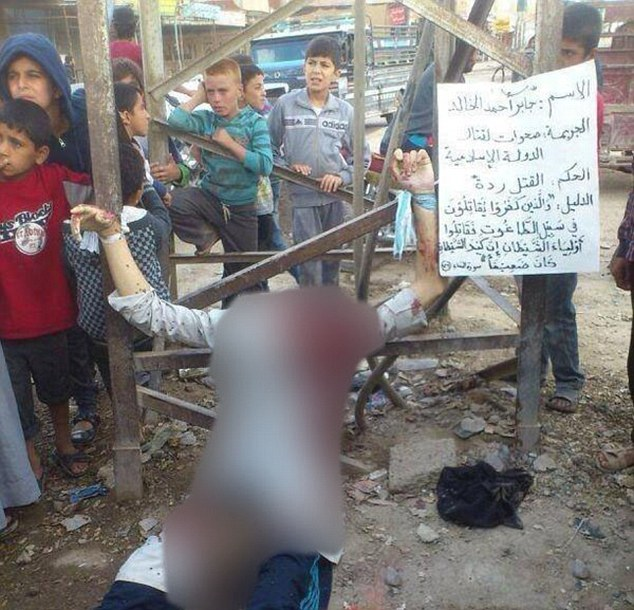 A photo of children crowding around the body of a crucified and beheaded Syrian rebel member has emerged