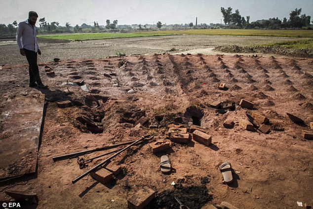 A man surveys the site of the brick kiln where the Christian couple were murdered. Only their discarded shoes, and some charred bones, remained of them