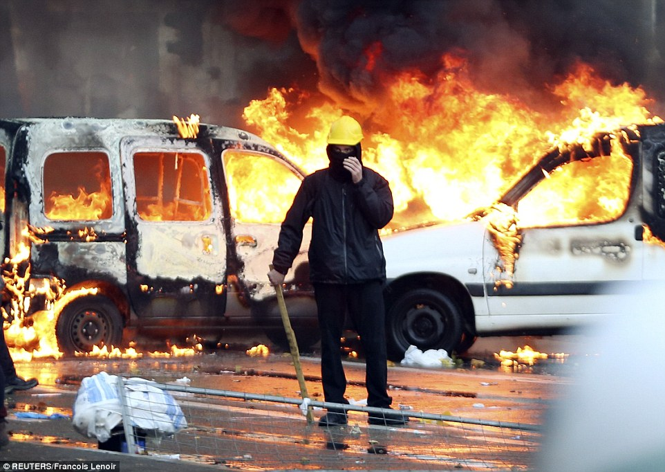 Armed: A protester stands in front of burning vehicles with a makeshift club to defend himself from police